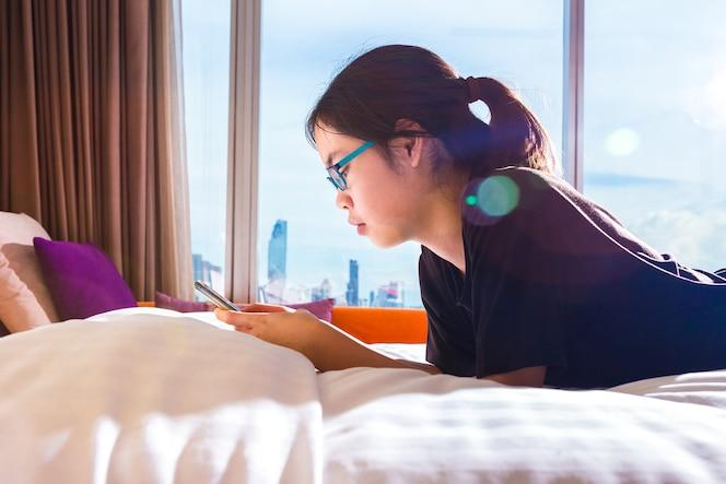 Adolescente mujer asiática usando su teléfono inteligente en la cama, la luz del sol de la mañana con la llamarada