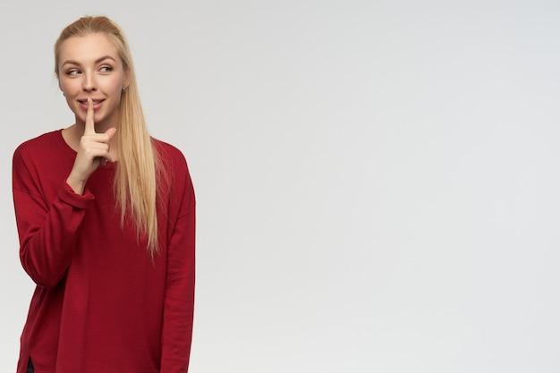 Adolescente, mujer de aspecto feliz con cabello largo rubio. llevaba un suéter rojo. concepto de personas y emociones. mirando a la derecha en el espacio de la copia, aislado sobre fondo blanco, muestra el signo de silencio