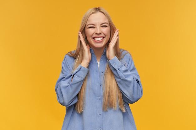 Adolescente, mujer de aspecto feliz con cabello largo rubio. vistiendo camisa azul. concepto de personas y emociones. entrecerrar los ojos por la emoción y sonreír ampliamente. mirando a la cámara, aislada sobre fondo naranja