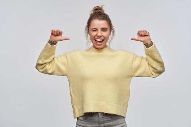Adolescente, mujer de aspecto feliz con cabello rubio reunido en moño y tatuajes. llevaba un suéter amarillo. señalándose a sí misma con los pulgares. mirando y guiñando un ojo a la cámara, aislada sobre pared blanca