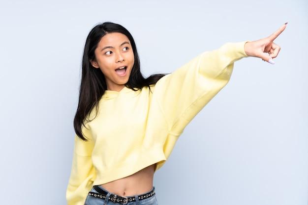 Adolescente mujer china en la pared azul apuntando lejos