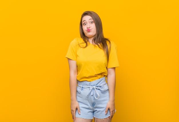 Adolescente mujer joven con una camisa amarilla sopla las mejillas, tiene expresión cansada. concepto de expresión facial.