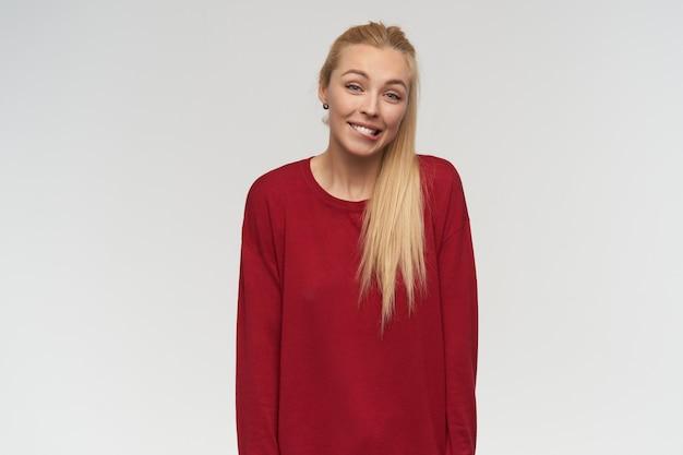 Adolescente, mujer de mirada confundida con cabello largo rubio. llevaba un suéter rojo. concepto de personas y emociones. mirando a la cámara, aislada sobre fondo blanco, mordiéndose el labio y levantando las cejas