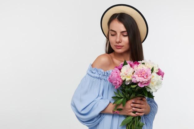 Adolescente, mujer de mirada feliz con cabello largo morena. con sombrero y vestido azul. sosteniendo un ramo de hermosas flores. mirando a la esquina inferior izquierda en el espacio de la copia sobre la pared blanca