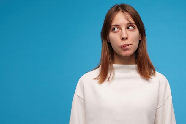 Adolescente, mujer de mirada maravilla con cabello moreno. vistiendo suéter blanco. mordiéndose el labio, pensando. concepto de personas. mirando a la izquierda en el espacio de la copia, aislado sobre la pared azul