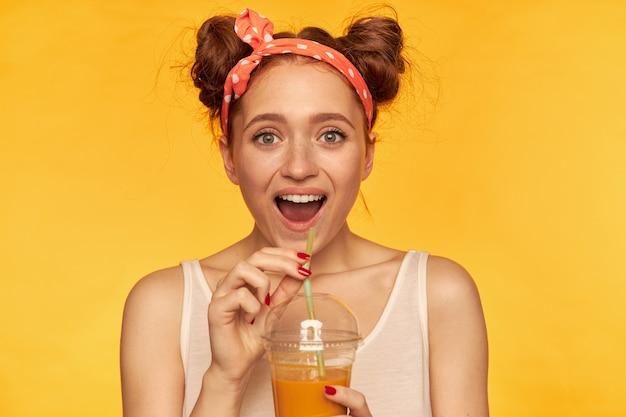Adolescente, mujer de pelo rojo de aspecto feliz con bollos. vistiendo camisa blanca y diadema roja adornada. luciendo emocionada y sosteniéndola jugosa fresca. mirando aislado sobre pared amarilla