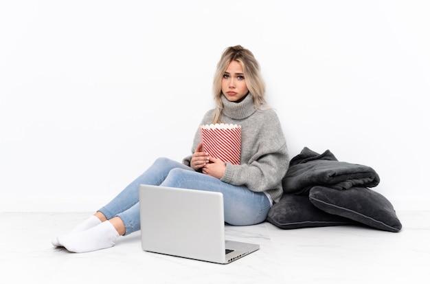 Adolescente mujer rubia comiendo palomitas de maíz mientras ve una película en la computadora portátil con expresión triste y deprimida