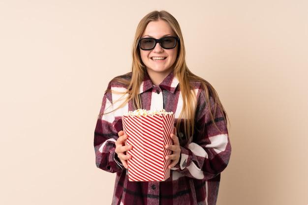 Adolescente mujer ucraniana aislada en espacio beige con gafas 3d y sosteniendo un gran cubo de palomitas de maíz