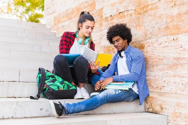 Adolescente multi étnica pareja sentada en la escalera estudiando juntos