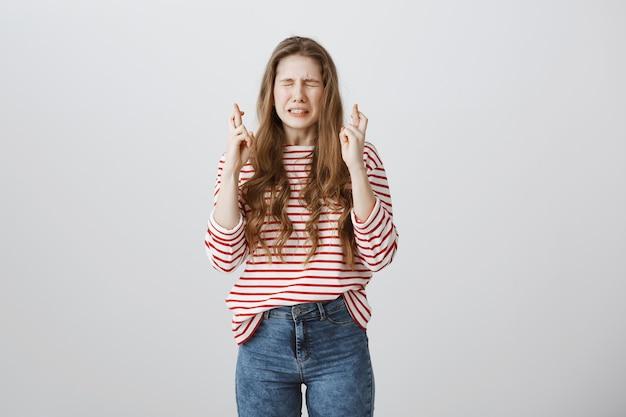 Adolescente nerviosa cerrar los ojos y cruzar los dedos, suplicando o pidiendo un deseo