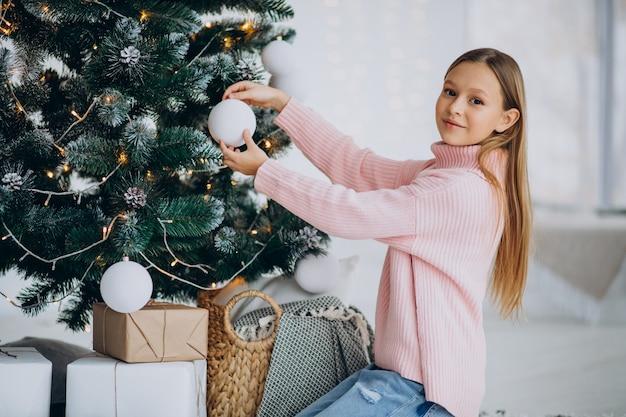 Adolescente niña decorar el árbol de navidad