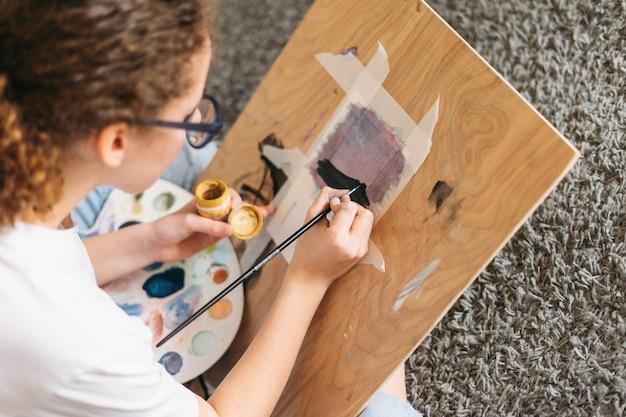 Adolescente niña de pelo rizado en gafas en camiseta blanca sentado en la pintura del suelo en el escritorio de madera en la casa
