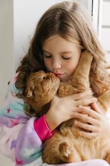 Adolescente niña se sienta en pijama en la ventana de la casa y sostiene un gato de jengibre. quedarse en casa.