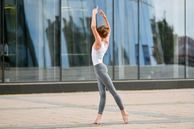 Adolescente niño de ballet bailando en el contexto del reflejo de la ciudad y el cielo en la pared de cristal