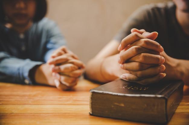 Adolescente orando junto con la biblia en casa