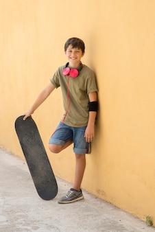 Un adolescente con patineta en la calle de la ciudad.