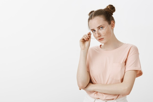 Adolescente pelirroja arrogante escéptica posando contra la pared blanca