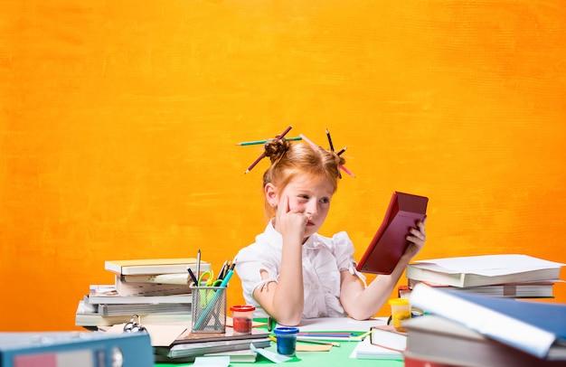La adolescente pelirroja con muchos libros en casa.