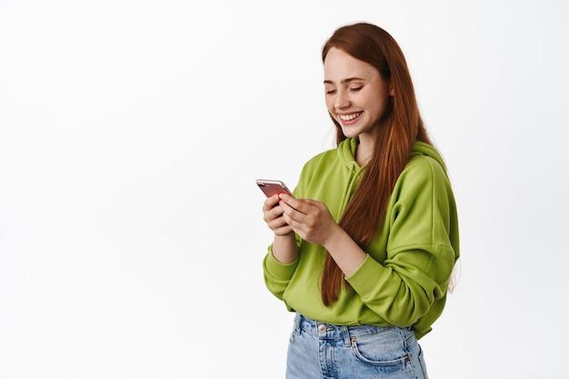 Adolescente pelirroja sonriendo y leyendo el teléfono inteligente, comunicándose a través de la aplicación móvil, chateando y enviando mensajes, de pie en blanco