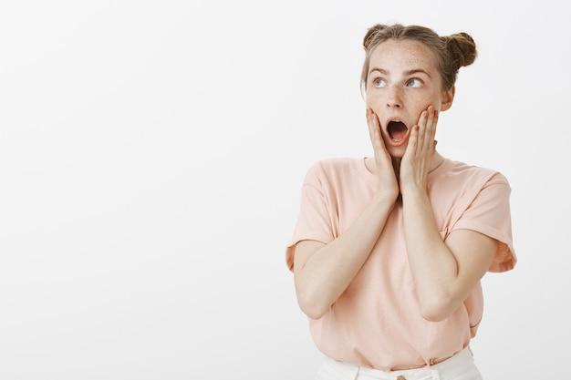 Adolescente pelirroja sorprendida e impresionada posando contra la pared blanca