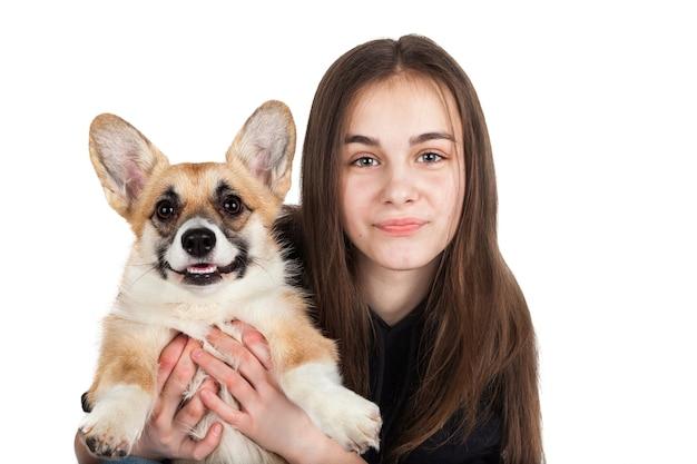 Adolescente de pelo castaño caucásico con cachorro de perro corgi sobre fondo blanco.