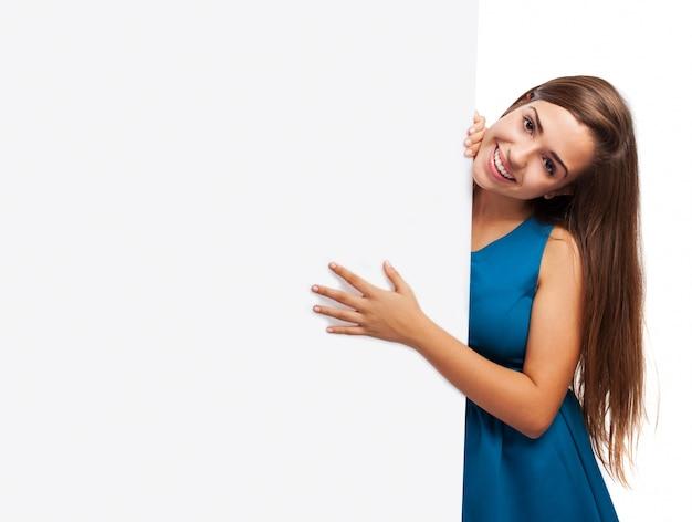 Adolescente de pelo largo con una mano sobre un letrero en blanco