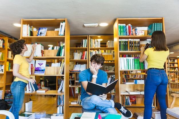 Adolescente pensativo leyendo cerca de amigas