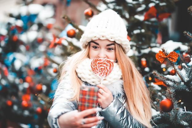 Adolescente con piruleta haciendo selfie con el árbol de navidad