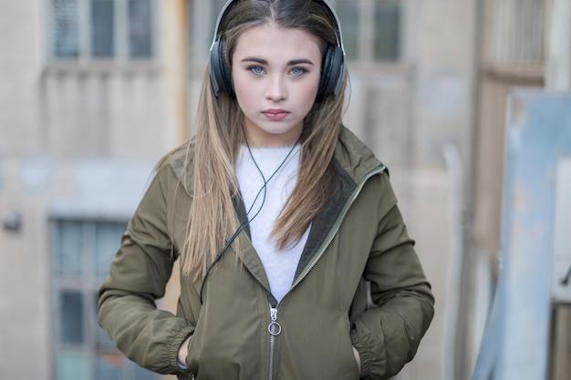 Adolescente posando escuchando música con auriculares