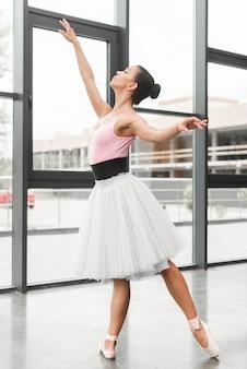 Adolescente practicando ballet dance cerca de la pared de cristal