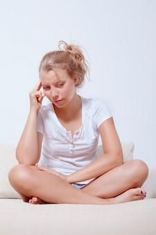 Adolescente preocupado se sienta con las piernas cruzadas sosteniendo la cabeza entre las manos