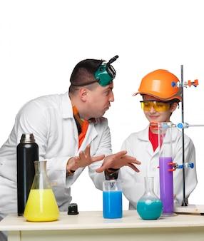 Adolescente y profesor de química en la lección haciendo experimentos
