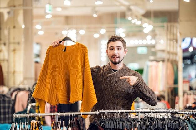 Un adolescente que ayuda a su novia a encontrar el suéter adecuado en una tienda de ropa.