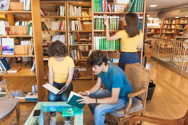 Adolescente que elige el libro cerca de amigos de lectura