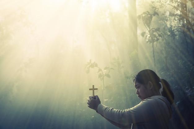 Adolescente que ruega con la cruz en naturaleza soleada.