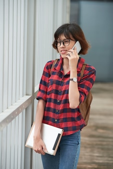 Adolescente en ropa casual llamando a un amigo mientras caminaba de la escuela