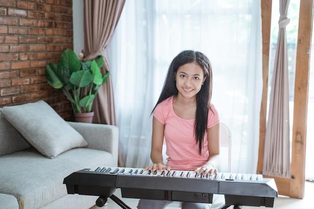Adolescente en ropa rosa aprende a tocar un instrumento de piano
