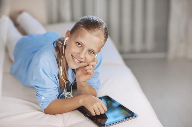 Adolescente rubia acostada en el sofá juega un juego en la tableta y se comunica a través de un enlace de video con amigos