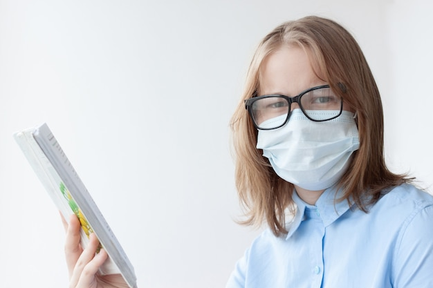 Una adolescente, rubia, con una camisa azul, una máscara médica y gafas sobre un fondo blanco, mira a la cámara, sosteniendo un libro de texto en la mano.
