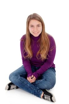 Adolescente rubio adorable que mira la cámara que se sienta en piso