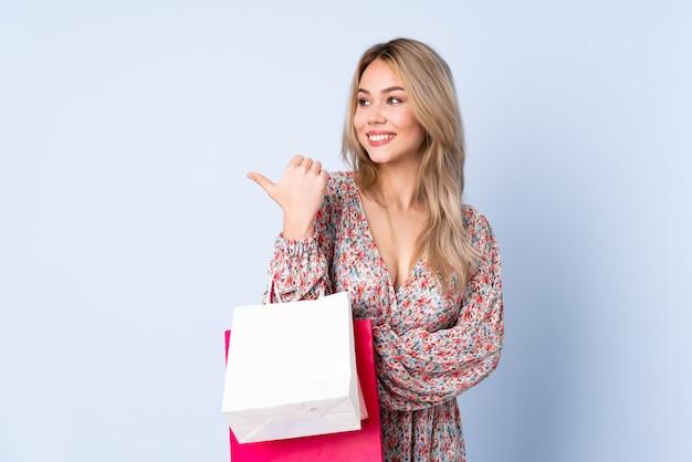 Adolescente rusa con bolsa de compras en la pared azul apuntando hacia un lado
