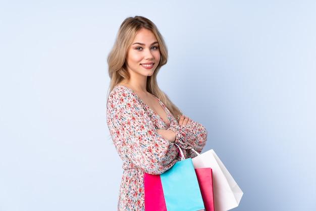 Adolescente rusa con bolsa de compras en la pared azul con los brazos cruzados y mirando hacia adelante