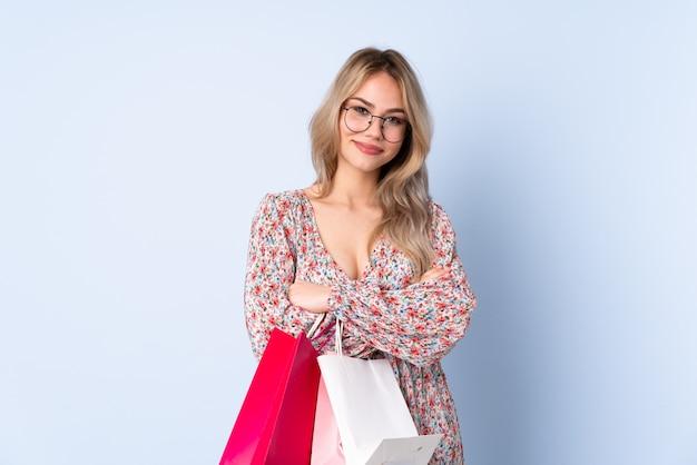 Adolescente rusa con bolsa de compras en la pared azul con gafas y sonriente
