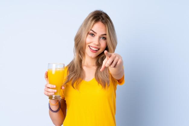 Adolescente rusa sosteniendo un jugo de naranja en la pared azul te señala con una expresión segura