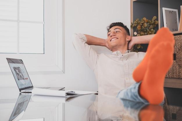Adolescente satisfecho feliz de terminar el trabajo con la computadora portátil en casa, levanta las manos y pone los pies sobre la mesa, relajándose después de un duro día de trabajo a la espera de una licencia de fin de semana, día de trabajo relajado, sin estrés