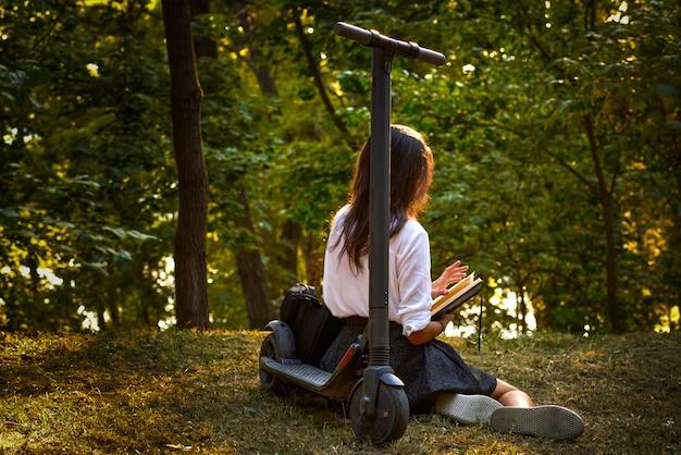 Adolescente de secundaria leyendo su diario cerca del scooter eléctrico
