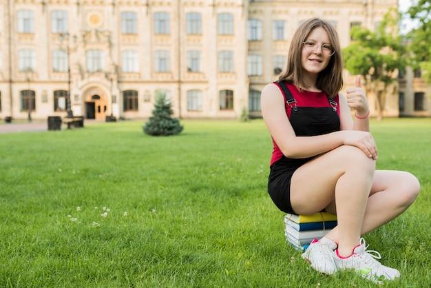 Adolescente sentada en libros frente a la escuela secundaria