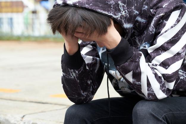 Adolescente sentado agacharse la cabeza. se siente frustrado y con depresión mayor.