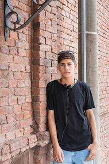 Adolescente serio que se inclina en la pared de ladrillo con el auricular negro que rodea su cuello