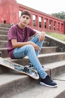 Adolescente serio que se sienta en las escaleras con el monopatín que mira lejos